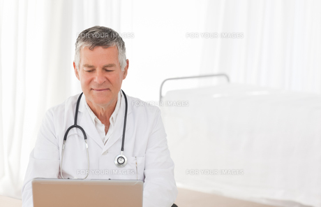 A senior doctor working on his laptop in his officeの写真素材 [FYI00483713]