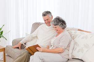 Senior couple looking at their photo albumの写真素材 [FYI00483716]