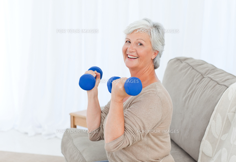 Senior doing her exercises on her sofaの写真素材 [FYI00483723]