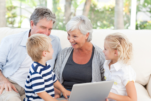 Adorable family looking at their laptopの写真素材 [FYI00483772]