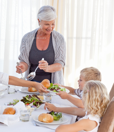 Grandmother giving other family members some food during the mealの写真素材 [FYI00483800]