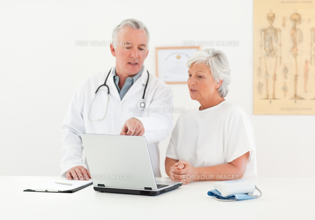 Doctor and his patient looking at the laptopの素材 [FYI00483831]
