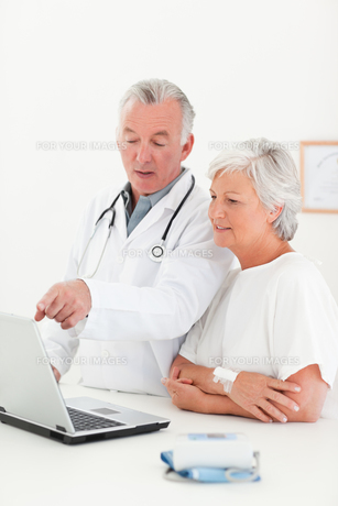 Doctor and his patient looking at the laptopの素材 [FYI00483832]