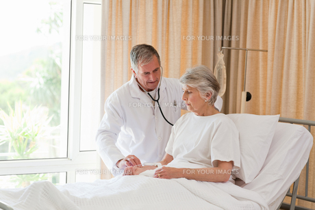 Senior doctor taking the heartbeat of his patientの素材 [FYI00483837]