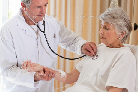 Senior doctor taking the heartbeat of his patientの素材 [FYI00483838]