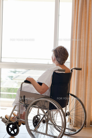 Senior woman in her wheelchair looking out the windowの素材 [FYI00483839]
