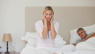 Woman having a headache while her husband is sleepingの素材 [FYI00483843]
