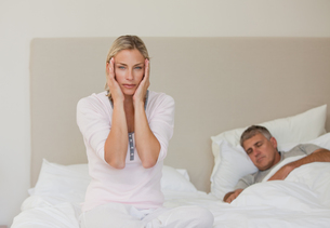 Woman having a headache while her husband is sleepingの写真素材 [FYI00483858]