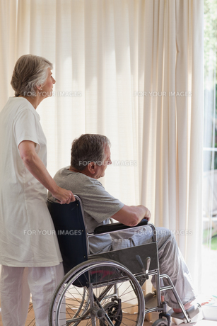 Retired couple looking out the windowの素材 [FYI00483865]
