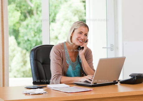 Woman working on her computer while she is phoningの写真素材 [FYI00483867]