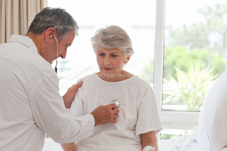 Senior doctor taking the heartbeat of his patientの素材 [FYI00483874]