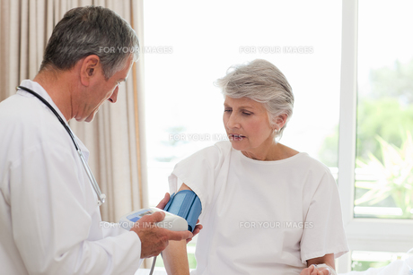 Doctor taking the blood pressure of his patientの素材 [FYI00483876]