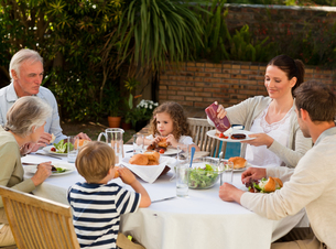 Adorable family eating in the gardenの写真素材 [FYI00483889]