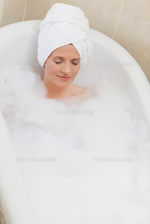 Lovely woman taking a bath with a towel on her headの素材 [FYI00483919]