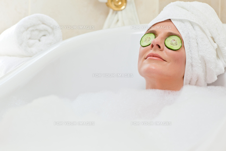 Relaxed woman taking a bath with a towel on her headの素材 [FYI00483922]