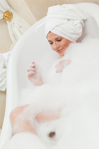 Lovely woman taking a bath with a towel on her headの素材 [FYI00483924]