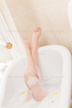 Pretty woman taking a relaxing bath with a towel on her headの素材 [FYI00483925]