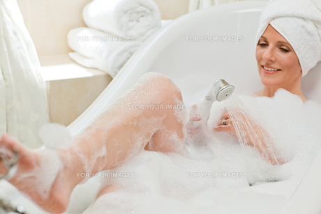 Smiling woman taking a bath with a towel on her headの素材 [FYI00483927]