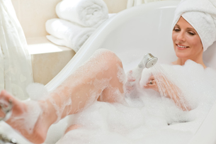 Smiling woman taking a bath with a towel on her headの写真素材 [FYI00483927]
