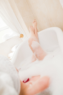 Pretty woman taking a relaxing bath with a towel on her headの写真素材 [FYI00483930]