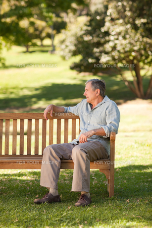 Elderly man sitting on a benchの写真素材 [FYI00483965]