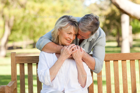 Elderly man hugging his wife who is on the benchの写真素材 [FYI00483972]