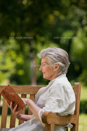 Retired woman reading a book on the benchの写真素材 [FYI00483976]