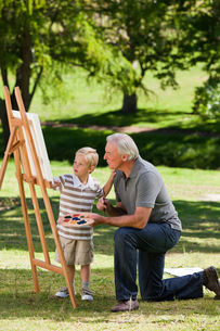 Grandfather and his grandson painting in the gardenの写真素材 [FYI00483979]
