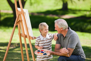 Grandfather and his grandson painting in the gardenの写真素材 [FYI00483983]