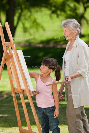 Grandmother and her granddaughter painting in the gardenの写真素材 [FYI00483992]