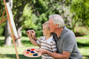 Happy Grandfather and his grandson painting in the gardenの写真素材 [FYI00483993]