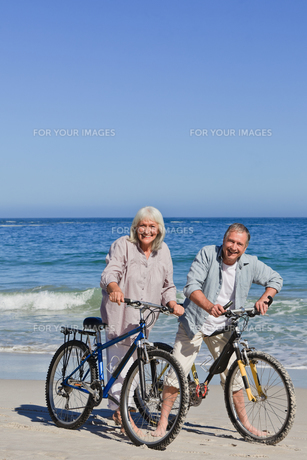 Mature couple with their bikes on the beachの素材 [FYI00483999]