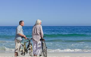 Senior couple with their bikes on the beachの写真素材 [FYI00484002]