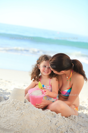 Daughter with her mother making a sand castleの写真素材 [FYI00484004]
