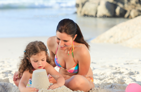 Daughter with her mother making a sand castleの素材 [FYI00484005]