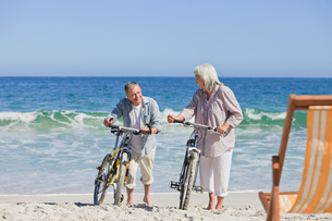 Elderly couple with their bikes on the beachの素材 [FYI00484009]