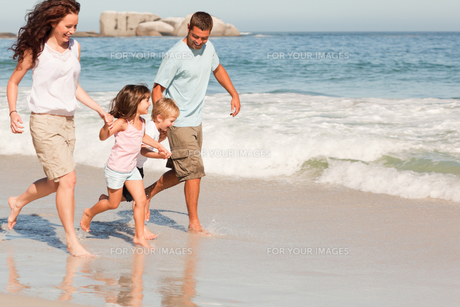 Family running on the beachの写真素材 [FYI00484020]