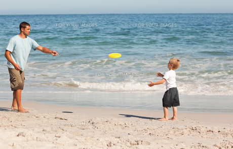 Little boy playing frisbee with his fatherの素材 [FYI00484021]
