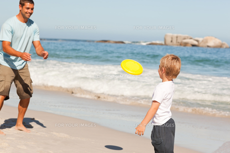 Little boy playing frisbee with his fatherの素材 [FYI00484022]