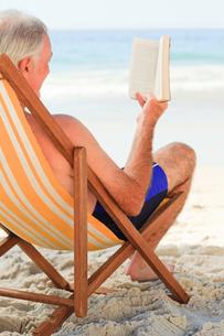 Senior man reading a book at the beachの素材 [FYI00484031]