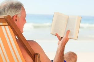 Senior man reading a book at the beachの素材 [FYI00484032]