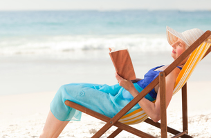 Elderly woman reading a book at the beachの素材 [FYI00484033]
