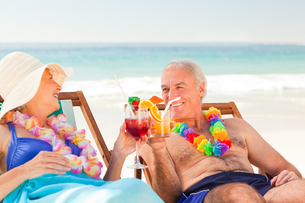 Couple drinking cocktails at the beachの写真素材 [FYI00484034]