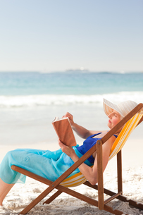 Elderly woman reading a book at the beachの素材 [FYI00484036]