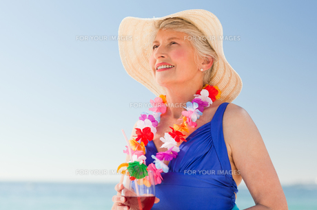 Elderly woman drinking a cocktail on the beachの写真素材 [FYI00484039]