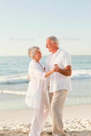 Elderly couple dancing on the beachの写真素材 [FYI00484043]