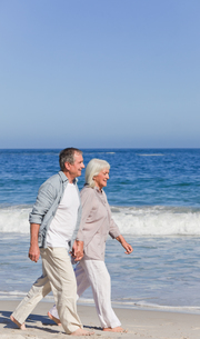 Elderly couple walking on the beachの写真素材 [FYI00484044]