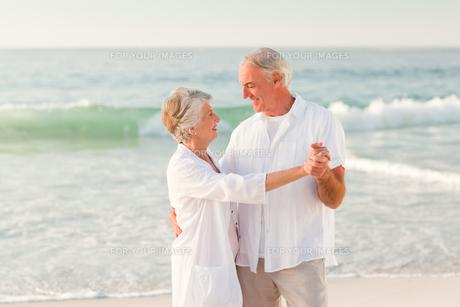 Elderly couple dancing on the beachの写真素材 [FYI00484045]