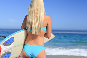 Beautiful blonde woman with her surfboardの写真素材 [FYI00484086]