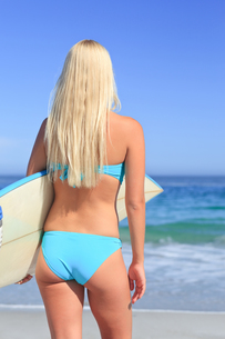 Beautiful blonde woman with her surfboardの写真素材 [FYI00484087]